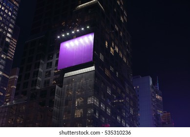 Illuminated billboard on side of a skyscraper.