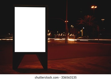 Illuminated blank billboard with copy space for your text message or content, public information board in night street, advertising mock up banner in metropolitan city, clear poster on roadside