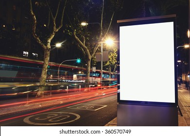 Illuminated blank billboard with copy space for your text message or content, public information board in night city with movement of car on background, advertising mock up banner in urban setting