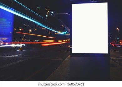 Illuminated blank billboard with copy space for your text message or content, public information board with shutter speed on background, advertising mock up in urban setting, empty poster on roadside