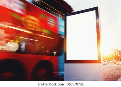 Illuminated blank billboard with copy space for your text message or content, public information board outdoors with motion blur bus on background, advertising mock up banner in metropolitan city