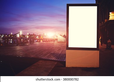 Illuminated blank billboard with copy space for your text message or promotional content, public information board in night in urban setting, advertising mock up banner in metropolitan city