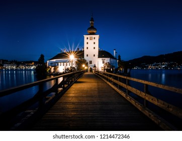 illuminated boardwalk to the Schloss Ort in Gmunden on the Traunsee at twilight hour