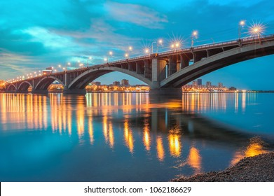 The illuminated bridge over the Yenisei River with reflection in the water on a summer evening, Krasnoyarsk, Russia.