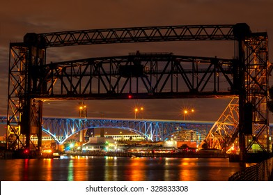 Illuminated bridges over the Cuyahoga River at Cleveland, Ohio, dominated by the railroad lift bridge in front