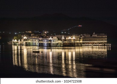 Illuminated buidling and boat over Lake Picholla, Udaipur, Rajasthan, India