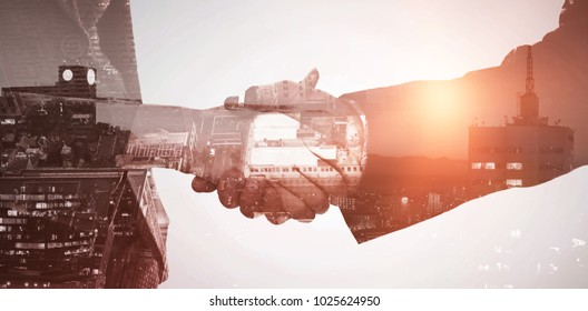 Illuminated buildings in city against sky against composite image of close up of two businesspeople shaking their hands