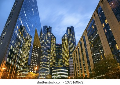 Illuminated business buildings in La Defense area in the evening, Paris, France