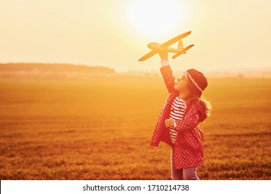 Illuminated by orange colored sunlight. Cute little girl have fun with toy plane on the beautiful field at daytime.