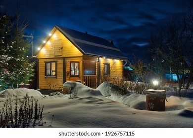 Illuminated by spotlights and outdoor lights the Russian wooden guest-house – banya framed by trees after heavy snowfall in winter twilight.