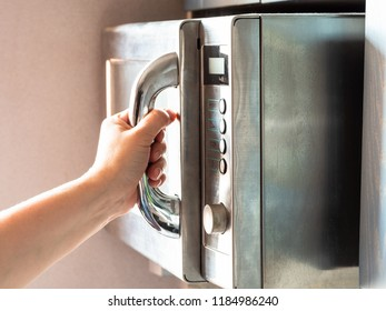 the illuminated by sun female hand opens an old microwave oven at home