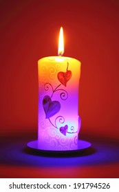 Illuminated candle with valentine decorations over red background