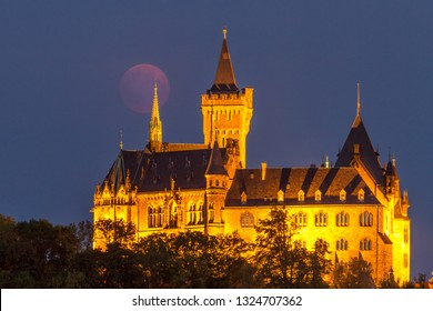 Illuminated castle at night with red full moon