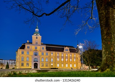 illuminated castle of Oldenburg (Germany) seen behind a leafless tree during blue hour at dawn