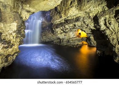 Illuminated Cave with Smooth Water