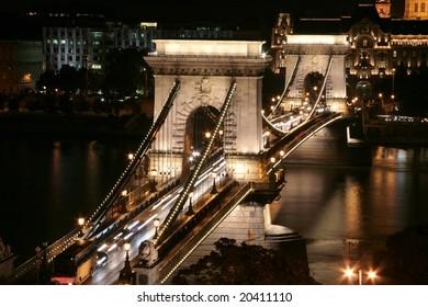 Illuminated chain bridge (Szechenyi Lanchid) in Budapest, Hunagary. Famous Hungarian landmark at night. Gresham Palace in the background.