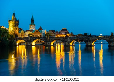 Illuminated Charles Bridge reflected in Vltava River. Evening in Prague, Czech Republic.