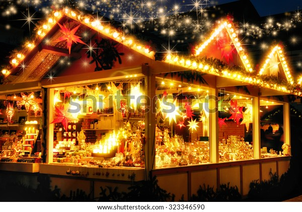 Illuminated Christmas fair kiosk with loads of shining decoration merchandise, no logos, with glittering magical stars raining down