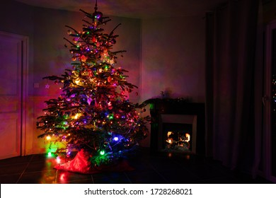 Illuminated Christmas tree in different color lights at night near burning fireplace fire