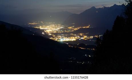Illuminated city in the Alps at night