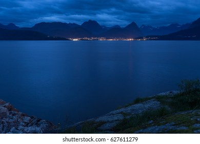 Illuminated city in front of a mountain range in Norway
