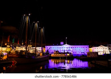 Illuminated city hall and old wooden sailing ship with tall masts at night in Helsinki, Finland