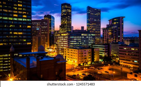 Illuminated city lights in Denver , Colorado , USA at Night Downtown City glowing Nightscape Skyline of the Mile High City Skyscrapers and office buildings rising up into the night sky