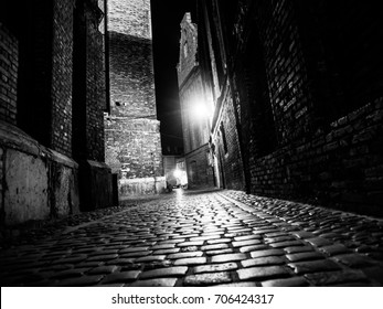 Illuminated cobbled street with light reflections on cobblestones in old historical city by night. Black and white image.