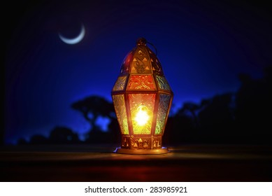 An illuminated colorful ramadan lantern against blue night sky with an crescent moon.