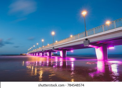 illuminated concrete pier in Kolobrzeg, long exposure shot at sunset