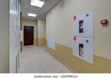 Illuminated corridor in modern  residential building with iron doors fire alarm on wall. Fire hose (or firehose) is a high-pressure hose that carries water or other fire retardant (such as foam)