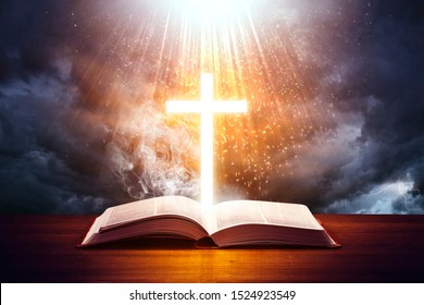 Illuminated cross on a Holy Bible. with a dramatic background sky.
