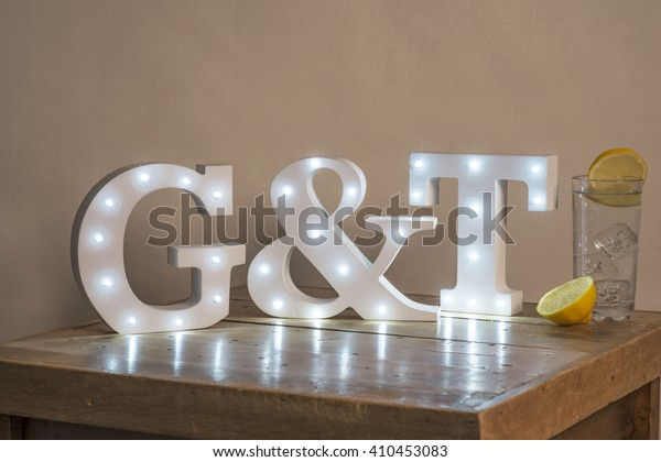 """Illuminated decorative letters that spell """"G&T"""" beside a glass of gin and tonic with lemon slices on a wooden surface."""