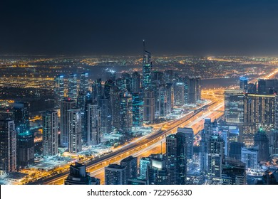 Illuminated Dubai Marina area with skyscrapers and highway at night, Dubai, UAE