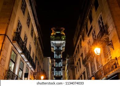 Illuminated elevador de Sant Justa (Santa Justa Lift) at night, as seen from a narrow street in Baixa, Lisbon.