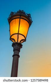 Illuminated Elizabethan streetlamp at twilight