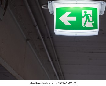 An illuminated emergency exit sign hangs on the ceiling of a parking garage.
