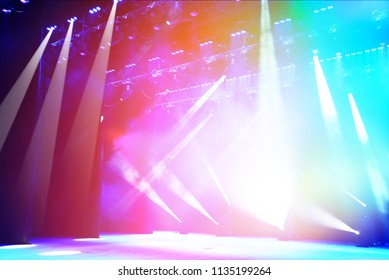 Illuminated empty concert stage with haze and rays of multicolored light. Background for music show