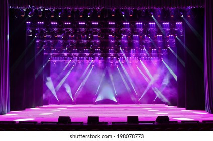 Illuminated empty magenta concert stage with fog and rays of light
