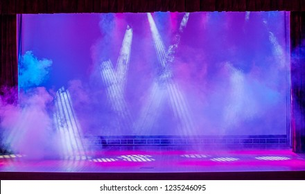 Illuminated empty show stage with fog, red and blue scenic light and white rays