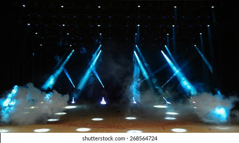 Illuminated empty theater stage with fog and rays of light