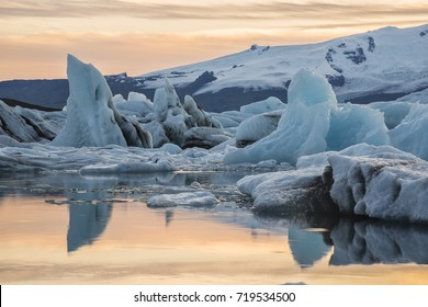 Illuminated with evening sun sky is reflected in water. Blue ices as rocks in the middle of composition. Iceland.