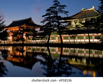 Illuminated evening view of the inner gate and wall surrounding Todai-ji temple with a pond in the foreground in Nara, Japan.  Todai-ji temple can be seen in the background behind the wall.
