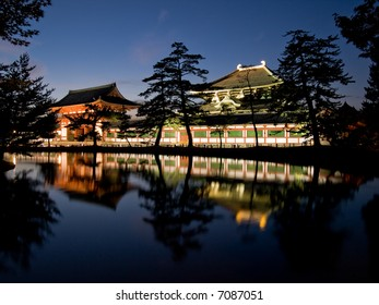 Illuminated evening view of the inner gate and wall surrounding Todaiji temple with a pond in the foreground in Nara, Japan.  Todai-ji temple can be seen in the background behind the wall.