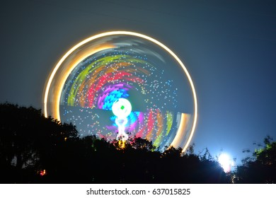 Illuminated fairground rides reflect from the River Medina at the Isle of Wight Music Festival in Newport on the Isle of Wight.