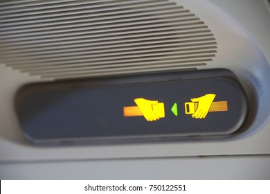 Illuminated Fasten Seatbelt Sign Next to Air Vent on the Ceiling in a Commercial Jet Waiting for Takeoff