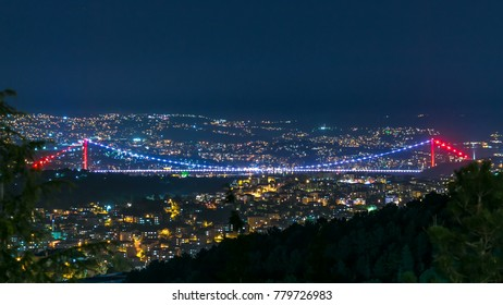 Illuminated Fatih Sultan Mehmet Bridge view, connects Asia and Europe night timelapse from top of Camlica hill. Istanbul, Turkey. City skyline on background