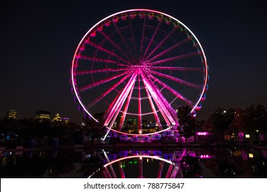 Illuminated ferris wheel in the Old Port of  Montreal. Long exposure night scene with motion blur to the wheel and reflection, with the modern architecture of the city of Montreal in the background.