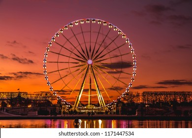 Illuminated Ferris wheel at sunset, Colorful sky and Ferris wheel.