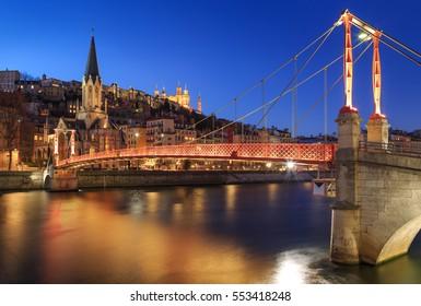 Illuminated footbridge Saint Georges and the old city of Lyon, Vieux Lyon, at dusk. Lyon, France.